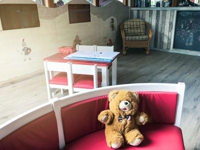 Ferdy's Gym Aldenhoven: Kinderbereich mit Teddybär auf roter bank