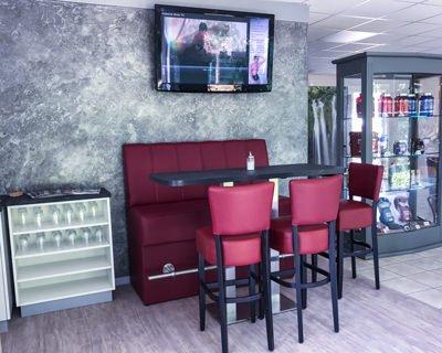 Bistro-Tisch mit Bank und Stühlen neben der Theke