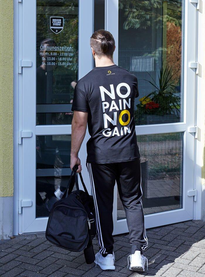 Junger Mann mit Statement-T-Shirt öffnet die Eingangstür vom Fitness Center